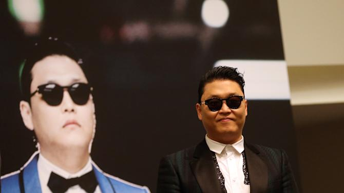 """FILE - In this Dec. 1, 2012 file photo, South Korean rapper PSY, who gained popularity from his famous song """"Gangnam Style,"""" gives a press conference prior to his concert at the Marina Bay Sands in Singapore. President Barack Obama still intends to attend a charity concert where PSY is scheduled to perform after reports the South Korean rapper participated in anti-American protests several years ago. (AP Photo/Wong Maye-E, File)"""