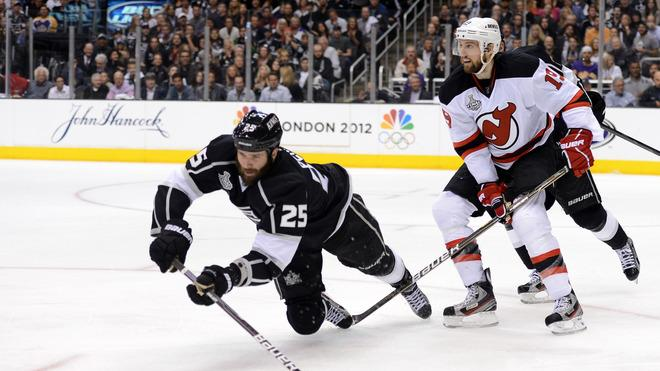 Dustin Penner #25 Of The Los Angeles Kings Dives To Play The Puck As Travis Zajac #19 Of The New Jersey Devils Looks  Getty Images