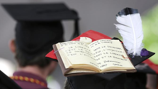 In this May 29, 2014 file photo, a graduating Harvard University student wears a mortarboard that features a book and a feather during Harvard commencement ceremonies, in Cambridge, Mass. To stand out amid a sea of caps and gowns at commencement, some graduating college students are decorating their mortarboards with messages, images and even 3-D creations.  (AP Photo/Steven Senne, File)