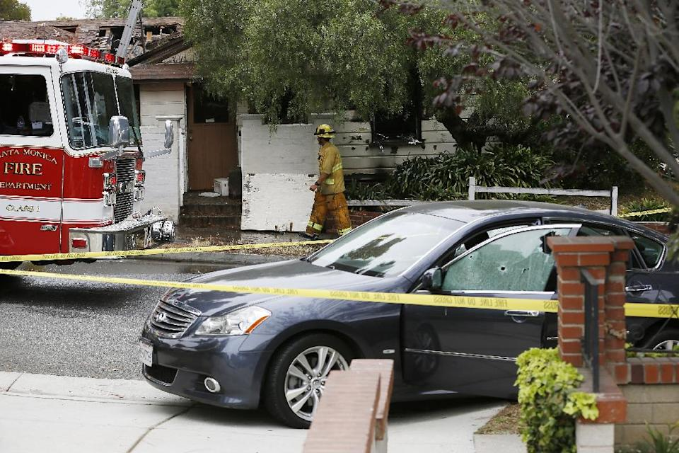 A firefighter walks past a car with bullet holes across a home that caught fire in Santa Monica, Calif. Friday, June 7, 2013. Two people were found dead Friday in a burned home near the school, where someone sprayed a street corner with gunfire, wounding at least three people, authorities said. (AP Photo/Damian Dovarganes)