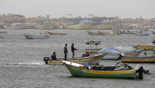 Palestinians ride a fishing boat at the seaport of Gaza City