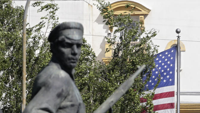 A monument to Russian revolutionary workers with the U.S. flag  and the U.S. Embassy in the background  seen in downtown Moscow, Russia, on Tuesday, May 14, 2013. Russia's security services said Tuesday that they detained a U.S. diplomat they claim is a CIA agent after they caught him red-handed trying to recruit a Russian agent. (AP Photo/Ivan Sekretarev)
