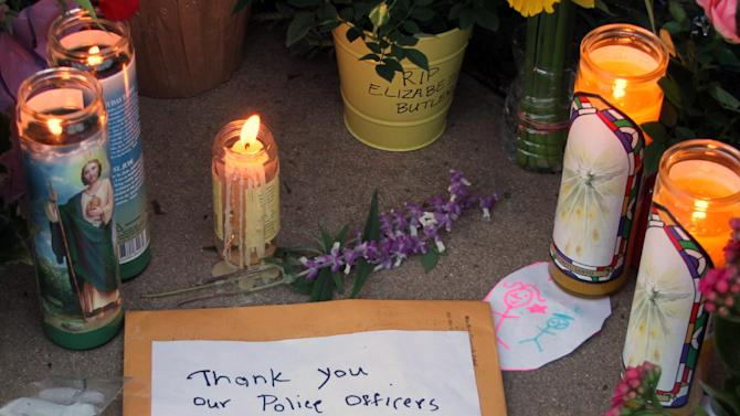 """A note is left at a memorial site for detectives Elizabeth Butler and Loran """"Butch"""" Baker at Santa Cruz Police Headquarters in Santa Cruz, Calif., Wednesday, Feb. 27, 2013. The detectives, responding to a sexual assault report Tuesday afternoon, were killed at the doorstep of a suspect who was chased down and killed half an hour later. (AP Photo/Thomas Mendoza)"""