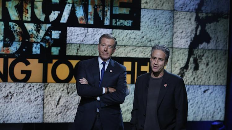 "In this photo provided by NBC, Brian Williams, left, and Jon Stewart perform during ""Hurricane Sandy: Coming Together"" Friday, Nov. 2, 2012, in New York. Hosted by Matt Lauer, the event is heavy on stars identified with New Jersey and the New York metropolitan area, which took the brunt of this week's deadly storm. (AP Photo/NBC, Heidi Gutman)"
