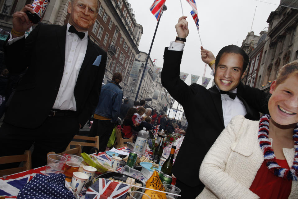 People wearing masks of the British Royals share in the Big Jubilee Lunch  at the Piccadilly Jubilee street party, in London Sunday June 3, 2012 to mark Queen Elizabeth II's 60 years on the British throne.(AP Photo/Elizabeth Dalziel)