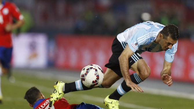 Argentina's Martin Demichelis jumps over Chile's Alexis Sanchez during their Copa America 2015 final soccer match at the National Stadium in Santiago