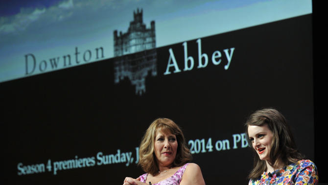 """FILE - This Aug. 6, 2013 file photo shows Sophie McShera, right, and Phyllis Logan, cast members in the Masterpiece series """"Downton Abbey,"""" take part in a panel discussion on the show at the PBS Summer 2013 TCA press tour in Beverly Hills, Calif. Millions around the world have been seduced by the straight-laced but stylish, old-fashioned but opulent world of the British drama. Soon they'll be able to take some of that style home, getting lips as soft as Lady Mary's, wine inspired by Lord Grantham's favorite tipple _ and even walls as gray as Mrs. Patmore's kitchen. Since it premiered in 2010, the series about the family and servants of a grand English country house in the 1910s and 1920s has become a television juggernaut, sold to 220 territories around the world. (AP Photo/Invision, Chris Pizzello, File)"""