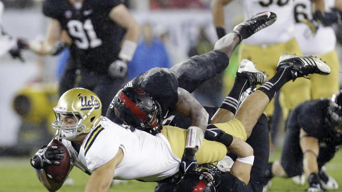 UCLA tight end Joseph Fauria is brought down after a reception against Stanford during the first half of the Pac-12 championship NCAA college football game in Stanford, Calif., Friday, Nov. 30, 2012. (AP Photo/Marcio Jose Sanchez)