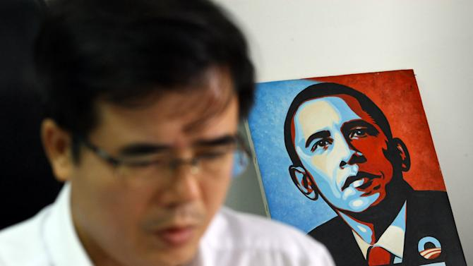 Le Quoc Quan, one of Vietnam's better-known dissidents and a leading blogger, works at his office in Hanoi, Vietnam on Friday, Sept. 28, 2012 with a painting of U.S. President Barack Obama. The Internet has become the principal staging ground for dissent in Vietnam, and its Communist rulers are trying to clamp down with new laws, stepped up arrests, intimidation and longer prison sentences. But so far, it's a battle they are losing. (AP Photo/Na Son Nguyen)