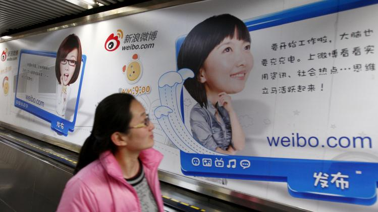 A woman looks at a Weibo advertisement as she rides an elevator inside a subway station in Beijing