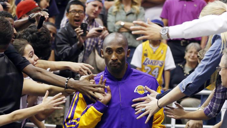 Los Angeles Lakers Kobe Bryant walks past fans before their NBA basketball game against the Utah Jazz in Salt Lake City