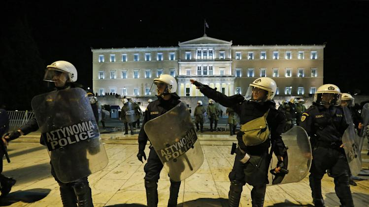 Greek riot police officers move to push the last remaining protesters, not seen, off the street,  in front of the Parliament in central Athens, Sunday, Nov. 11, 2012. Thousands of protesters converged peacefully on the Greek capital's main square outside the Parliament on Sunday evening, as lawmakers debated the 2013 budget, which includes pension and salary cuts demanded by the country's international creditors in order for them to approve the next vital batch of rescue loans. (AP Photo/Lefteris Pitarakis)