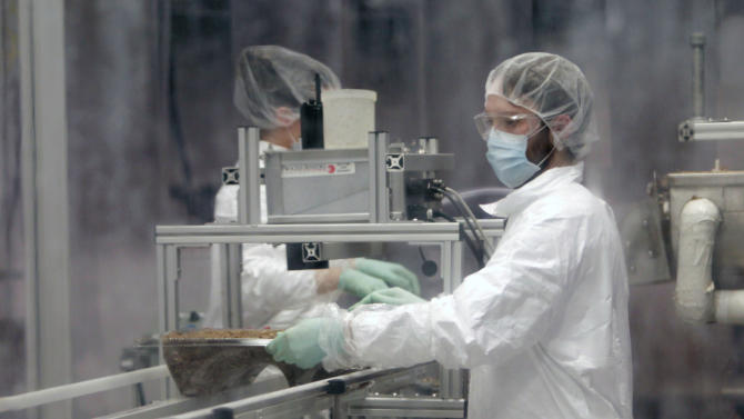 Jake Winiski performs quality control in a cleanroom inspecting a tray of mycelium and other raw materials that will age to become an eco-friendly packaging material at Ecovative Design in Green Island, N.Y., on Thursday, Feb. 9, 2012. (AP Photo/Mike Groll)