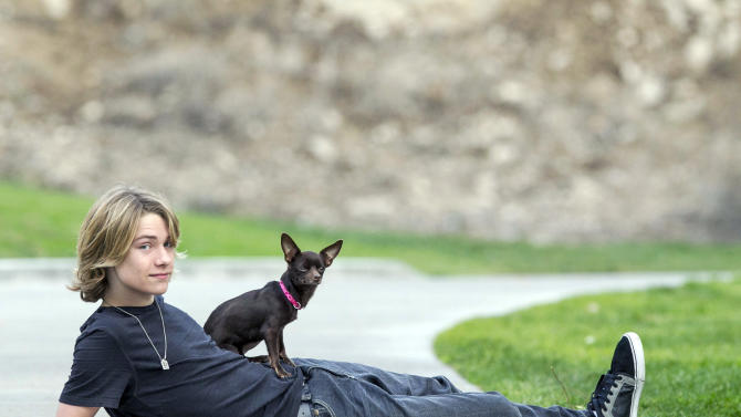 In this Nov. 16, 2012, photo, Lou Wegner, the founder of Kids Against Animal Cruelty, poses for a photo in Burbank, Calif., with his dog Pearl, who was rescued from a shelter. Lou, a 16-year-old actor and singer from Columbus, Ohio, started Kids Against Animal Cruelty when he was 14. The organization, which uses social networking to encourage adoptions at high-kill animal shelters, has helped 20,000 pets escape euthanasia in two years. (AP Photo/Damian Dovarganes)