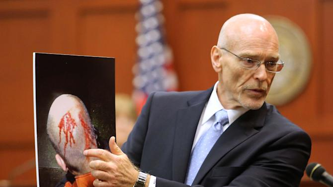 FILE - This June 24, 2013 file photo, Don West, a defense attorney for George Zimmerman, displays a photo of his client from the night of the shooting of Trayvon Martin, to the jury during opening statements in Zimmerman's trial, in Seminole circuit court, in Sanford, Fla. Zimmerman has been charged with second-degree murder for the 2012 shooting death of Trayvon Martin. (AP Photo/Orlando Sentinel, Joe Burbank, Pool)