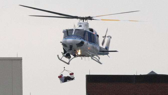 A U.S. Park Police helicopter removes a man in a basket from the Washington Navy Yard Monday, Sept. 16, 2013. Earlier in the day, the U.S. Navy said it was searching for an active shooter at the Naval Sea Systems Command headquarters, where about 3,000 people work. The exact number of people killed and the conditions of those wounded was not immediately known. (AP Photo/Jacquelyn Martin)