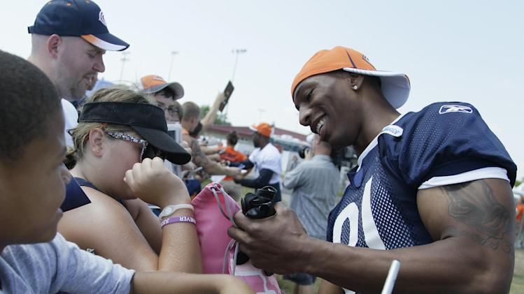 FILE - In this July 31, 2011 file photo, Chicago Bears wide receiver Sam Hurd, right, smiles as he signs autographs for fans before NFL football training camp at Olivet Nazarene University in Bourbonnais, Ill. The former wide receiver has pleaded guilty to a drug-possession charge that will likely result in a lengthy prison sentence. The 27-year-old Hurd pleaded guilty Thursday, April 11, 2013 in Dallas federal court. (AP Photo/Nam Y. Huh, File)