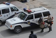 File photo shows two Tibetan Buddhist pilgrims looking at a police car outside the Labrang Monastery, the second largest Tibetan monastery in existence, in the town of Xiahe, Gansu Province. Chinese police are offering up to $16,000 as a reward for information on the &quot;black hands&quot; behind a string of self-immolations in a Tibetan-inhabited region