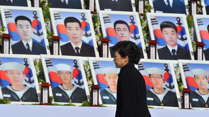 "South Korean President Park Geun-hye walks by the portraits of some of 46 South Korean sailors who were killed in the sinking of their war ship ""Cheonan,"" at the National Cemetery in Daejeon, South Korea, Tuesday, March 26, 2013. An explosion ripped apart the 1,200-ton warship, killing 46 sailors near the maritime border with North Korea in 2010. The sailors are buried here in the city. South Korea marks three years from the incident on March 26. (AP Photo/Kim Jae-hwan, Pool)"