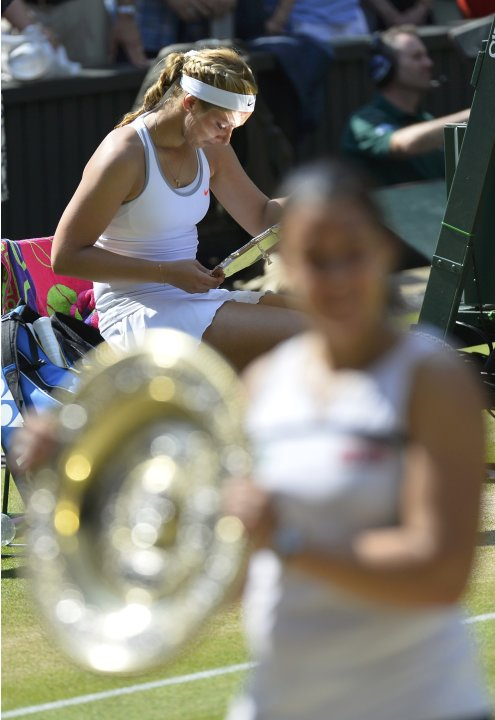 Sabine Lisicki of Germany looks at her runners-up trophy as Marion Bartoli of France holds her winners trophy, the Venus Rosewater Dish, after their women's singles final tennis match at the Wimbledon