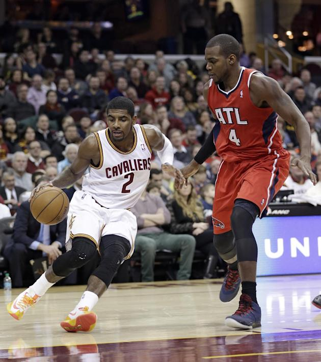 Cleveland Cavaliers' Kyrie Irving (2) drives past Atlanta Hawks' Paul Millsap (4) during the first quarter of an NBA basketball game Thursday, Dec. 26, 2013, in Cleveland