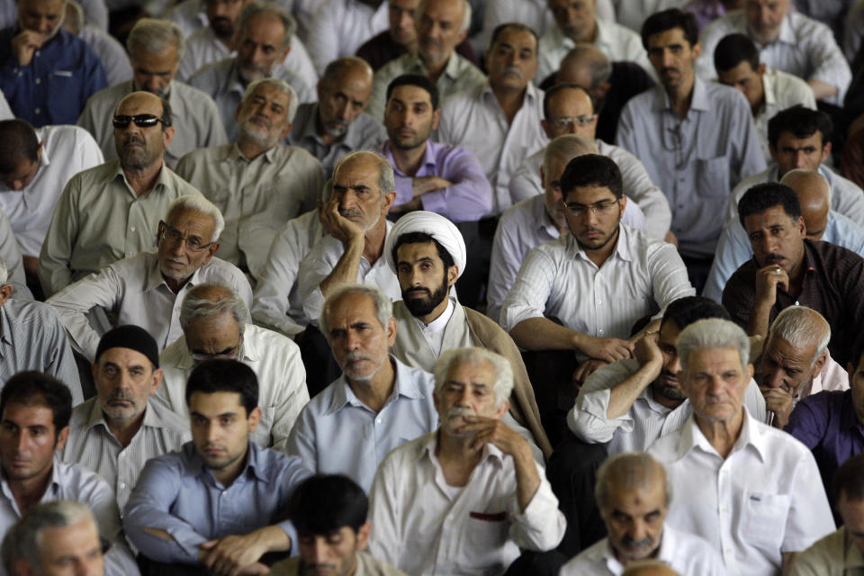 Iranian worshippers listen to a sermon during Friday prayers at Tehran University, in Tehran, Iran, Friday, July 6, 2012. Iranian Intelligence Minister, Heidar Moslehi, unseen, delivered a speech during Friday prayers accusing French and German intelligence services of cooperating with the CIA to kill Iranian nuclear scientists. (AP Photo/Vahid Salemi)