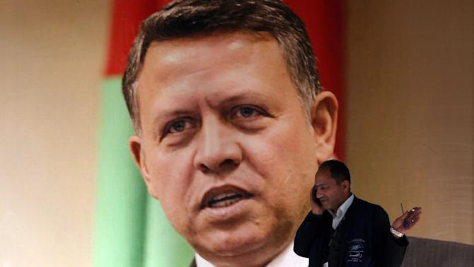 A member of the Jordanian Independent Electoral Commission, walks past a large photograph of King Abdullah II of Jordan, at the counting votes station in Amman, Jordan, Thursday, Jan. 24, 2013. Despite a wide boycott by Jordan's Muslim Brotherhood and other smaller opposition parties, at least three dozen Islamists who ran as independents have won seats in the kingdom's newly empowered parliament, according to initial results released Thursday. (AP Photo/Mohammad Hannon)