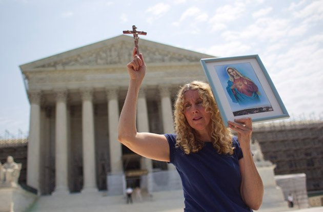 Carol Anderson of Williamsburg, Va., holds a cross outside the Supreme Court.