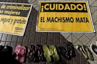 Shoes that belonged to murdered women, are shown next to signs protesting domestic violence in Santiago, Chile on July 30, 2009. More than half of Bolivian women have suffered domestic violence, according to a report out Thursday that found such abuse widespread in Latin America, with partners usually the perpetrators