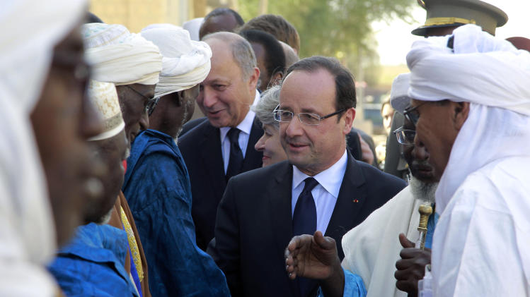 French President Francois Hollande, center, visits Timbuktu, Mali, Saturday, Feb. 2, 2013. The French leader is making a triumphant stop in the town, which French forces liberated six days ago from the al-Qaida-linked extremists who seized northern Mali last year. (AP Photo/Jerome Delay)