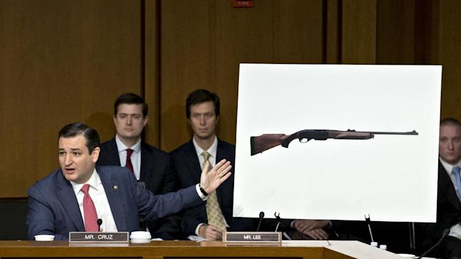 FILE - In this Jan. 30, 2013 file photo Sen. Ted Cruz, R-Texa,s points to a life size photo of a Remington 750, a popular hunting rifle, to make a point about the proposed ban on certain kinds of guns during a Senate Judiciary Committee on Capitol Hill in Washington. Weeks into his job, Texas Republicans are cheering Cruz's indelicate debut and embracing him as one of their own. The insurgent Republican elected with the tea party's blessing and bankroll, has run afoul of GOP mainstays, prompted Democrats to compare his style to McCarthyism. (AP Photo/J. Scott Applewhite, File)