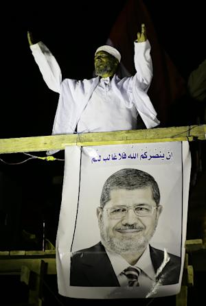 "A cleric addresses Islamist protesters supporting Egyptian President Mohammed Morsi, seen on poster, during a protest in front of the Media City complex in Giza, Egypt, Wednesday, Dec. 12, 2012. Egypt's main opposition alliance called for a ""No"" vote in the referendum on a disputed constitution rather than a boycott, hours after Islamist President Mohammed Morsi's government forged ahead by starting overseas voting in diplomatic missions for expatriates. The Arabic writing is a verse from the Quran. (AP Photo/Hassan Ammar)"