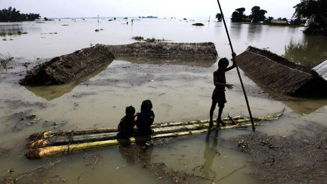 Young Indian children use a raft, made of banana plants, to wade through flood waters at Burhaburhi village, about 65 kilometers (40 miles) east of Guahati, India, Friday, June 29, 2012. Raging floodwaters fed by monsoon rains have inundated more than 2,000 villages in northeast India, killing at least 27 people and leaving hundreds of thousands more marooned Friday. (AP Photo/Anupam Nath)