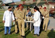Army doctors move Malala Yousafzai, 14, from a helicopter to an army hospital. She is being treated at the country's top military hospital in Rawalpindi, the twin city of the capital Islamabad, and on Saturday she showed signs of improvement by moving her hands and feet