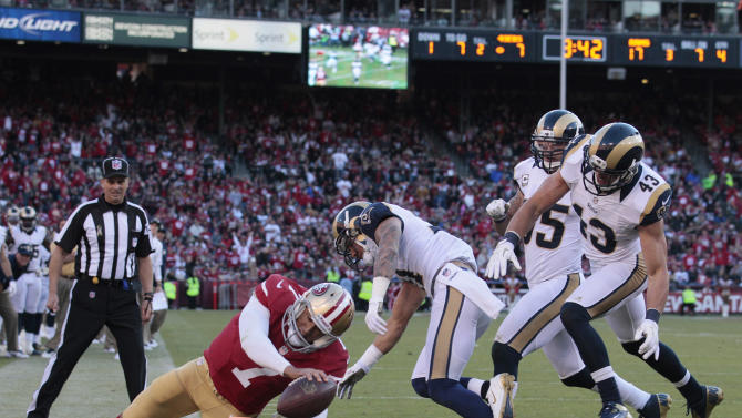 San Francisco 49ers quarterback Colin Kaepernick makes it across the goal line on a seven-yard touchdown run past St. Louis Rams strong safety Craig Dahl (43), middle linebacker James Laurinaitis, second from right, and St. Louis Rams cornerback Cortland Finnegan, third from right, during the fourth quarter of an NFL football game in San Francisco, Sunday, Nov. 11, 2012. (AP Photo/Jeff Chiu)