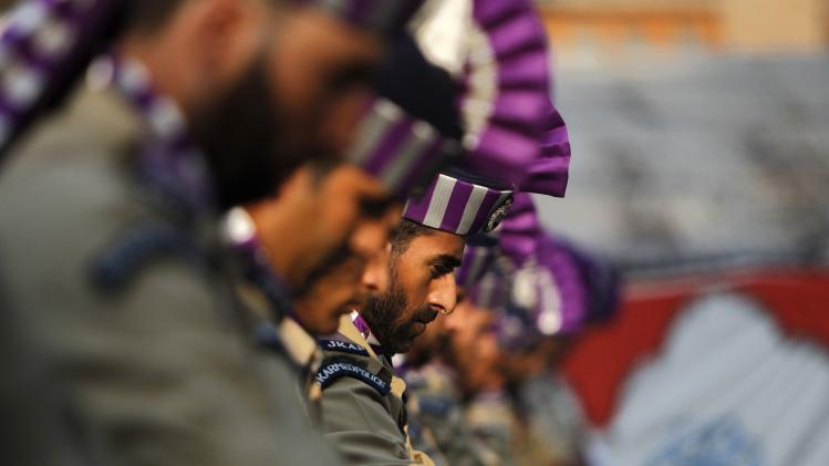 Indian policemen take part in a ceremony to mark Martyrs Day in Srinagar