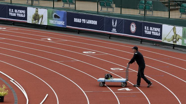 Equipment is removed at the U.S. Olympic Track and Field Trials on Monday, July 2, 2012 in Eugene, Ore. Jeneba Tarmoh has conceded her spot in the 100 meters rather than race against training partner Allyson Felix. Tarmoh notified USA Track and Field on Monday of her intention to withdraw. (AP Photo/Eric Gay)