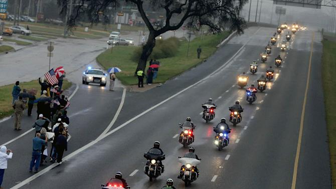 Supporters of Chris Kyle line up along the southbound lane of Interstate 35,Tuesday, Feb. 12, 2013, in Waco, Texas, for his journey to Austin, where he will be buried at the Texas State Cemetery. Kyle and his friend Chad Littlefield were shot and killed Feb 2. at a North Texas gun range. (AP Photo/Waco Tribune Herald, Rod Aydelotte)