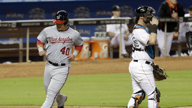 Washington Nationals' Wilson Ramos (40) scores as Miami Marlins catcher Jarrod Saltalamacchia (39) waits for the throw during a baseball game in Miami, Thursday, Sept. 18, 2014. (AP Photo/Alan Diaz)