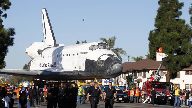 The Space Shuttle Endeavour is slowly moved down Martin Luther King Blvd. in Los Angeles Sunday, Oct. 14, 2012. In thousands of Earth orbits, the space shuttle Endeavour traveled 123 million miles. But the last few miles of its final journey are proving hard to get through. Endeavour's 12-mile crawl across Los Angeles to the California Science Museum hit repeated delays Saturday, leaving expectant crowds along city streets and at the destination slowly dwindling. Officials estimated the shuttle, originally expected to finish the trip early Saturday evening, would not arrive until later Sunday. (AP Photo/Alex Gallardo)