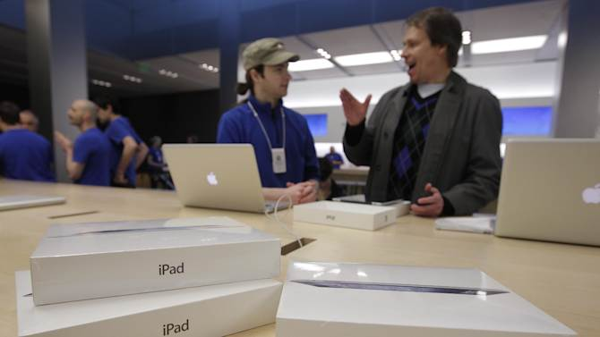 FILE - This March 16, 2012 file photo shows a customer talking with an Apple worker, in blue, inside an Apple store on the first day of the launch of the new iPad, in San Francisco. A research firm that has taken apart a new iPad says it's more expensive to make than the previous version was when it launched a year ago. The tablet's retail price is the same so that means Apple is making less from each sale. Since the first iPad, Apple has been pricing the tablet aggressively, making it hard for competitors to match its features for the same price. (AP Photo/Paul Sakuma)