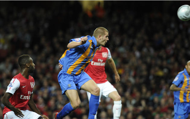 Shrewsbury Town's James Collins scores  the opening goal against Arsenal  during their English League Cup soccer match at the Emirates stadium, London, Tuesday, Sept. 20, 2011. (AP Photo/Tom Hevezi)