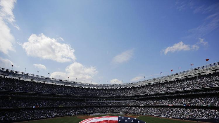 An American flag is held by West Point cadets in the Yankee Stadium outfield prior to the start of a baseball game against the Boston Red Sox,  Monday, April 1, 2013 in New York. (AP Photo/Mark Lennihan)