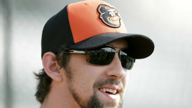 Former Olympic swimmer Michael Phelps waits to hit in the batting cage during a Baltimore Orioles baseball spring training workout Thursday, Feb. 21, 2013, in Sarasota, Fla.  Phelps, a native of Baltimore who was in the area filming his Golf Channel show The Haney Project, took batting practice with the team. (AP Photo/Charlie Neibergall)