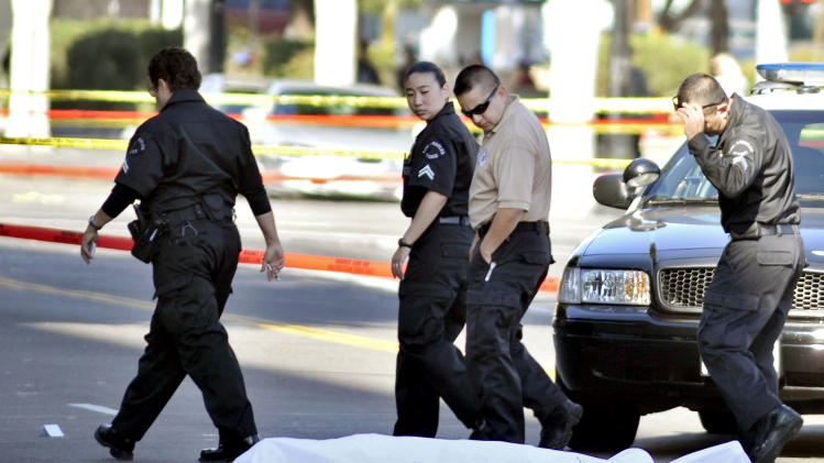 "Investigators look at a body at the scene of a fatal shooting, Friday,  Dec. 9, 2011, in the Hollywood are of Los Angeles, Calif. A gunman who fired at cars and shouted ""kill me"" and ""I'm gonna die!"" was shot to death Friday by police after wounding a driver in the heart of Hollywood, authorities and a witness reported. (AP Photo/Josh Edelson)"