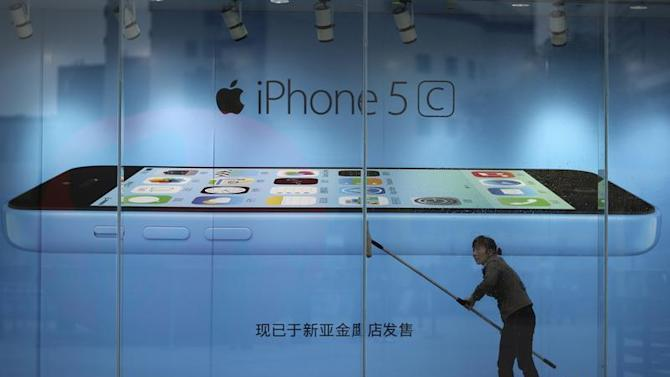 File picture shows a worker cleaning in front of an iPhone 5C advertisement at an apple store in Kunming