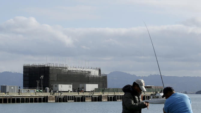 """FILE - In this Tuesday, Oct. 29, 2013, file photo, two men fish in the water in front of a Google barge on Treasure Island in San Francisco. The barge portion of the Google barge mystery is only half the story. When completed, the full package is envisioned to be an """"unprecedented artistic structure,"""" sporting a dozen or so gigantic sails, to be moored for a month at a time at sites around the bay. Documents submitted to the Port of San Francisco show that the barge's creators have big plans for the bulky box. (AP Photo/Jeff Chiu, File)"""
