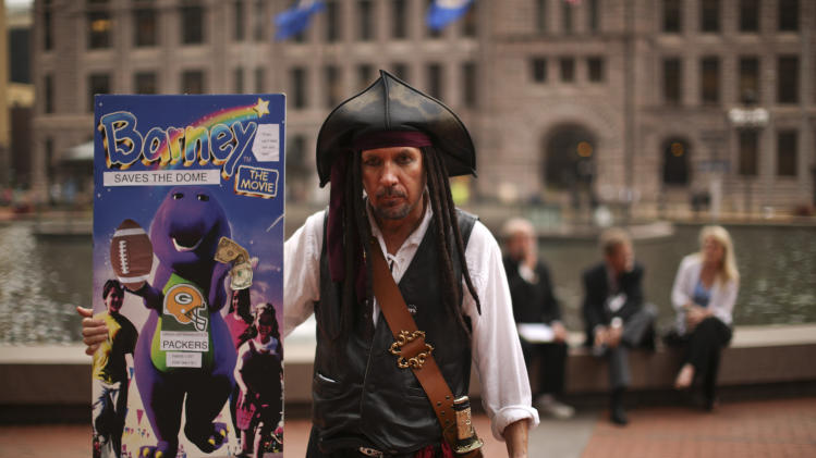 "In this Sept. 18, 2013 photo, Minneapolis mayoral candidate Capt. Jack Sparrow holds up a poster for a proposal he has put forward for community ownership of an NFL football team. Sparrow, who initially showed up at campaign events in full pirate drag, is a self proclaimed ""occupirate"" who espouses Occupy Wall Street ideology. (AP Photo/Star Tribune, Jeff Wheeler)"