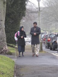 Malala Yousufzai walks with her father Ziauddin as she attends Edgbaston High School for girls in Edgbaston, central England in this handout photograph released March 19, 2013. Yousufzai, the Pakistani girl who attracted worldwide attention last year after she was shot in the head by the Taliban for advocating girls' education, was back at school on Tuesday in Britain where she was treated for her wounds. REUTERS/Edelman/Handout