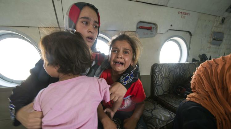 A woman and children react in a military helicopter after being evacuated by Iraqi forces from Amerli